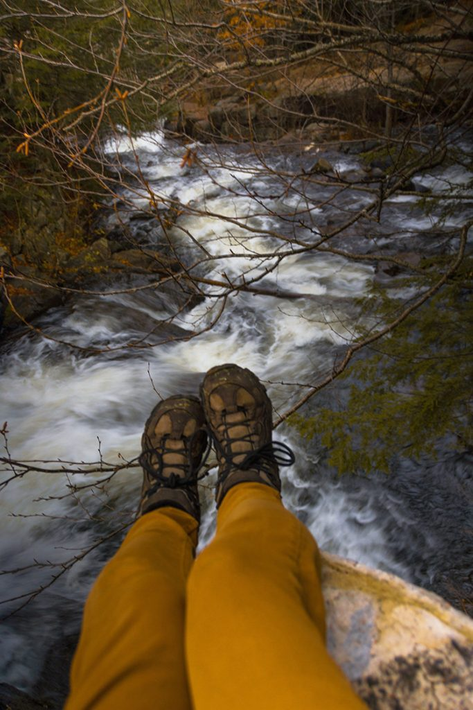A shot of a woman's legs and feet hanging over a cliff with waterfall rapids in the background