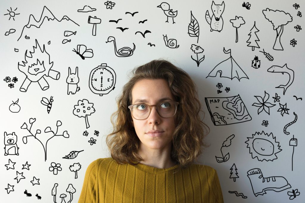Woman looks upwards imagining all the spring activities she wants to do. There are doodles of spring activities all around her (camping, map, compass, axe, mountains, flowers)
