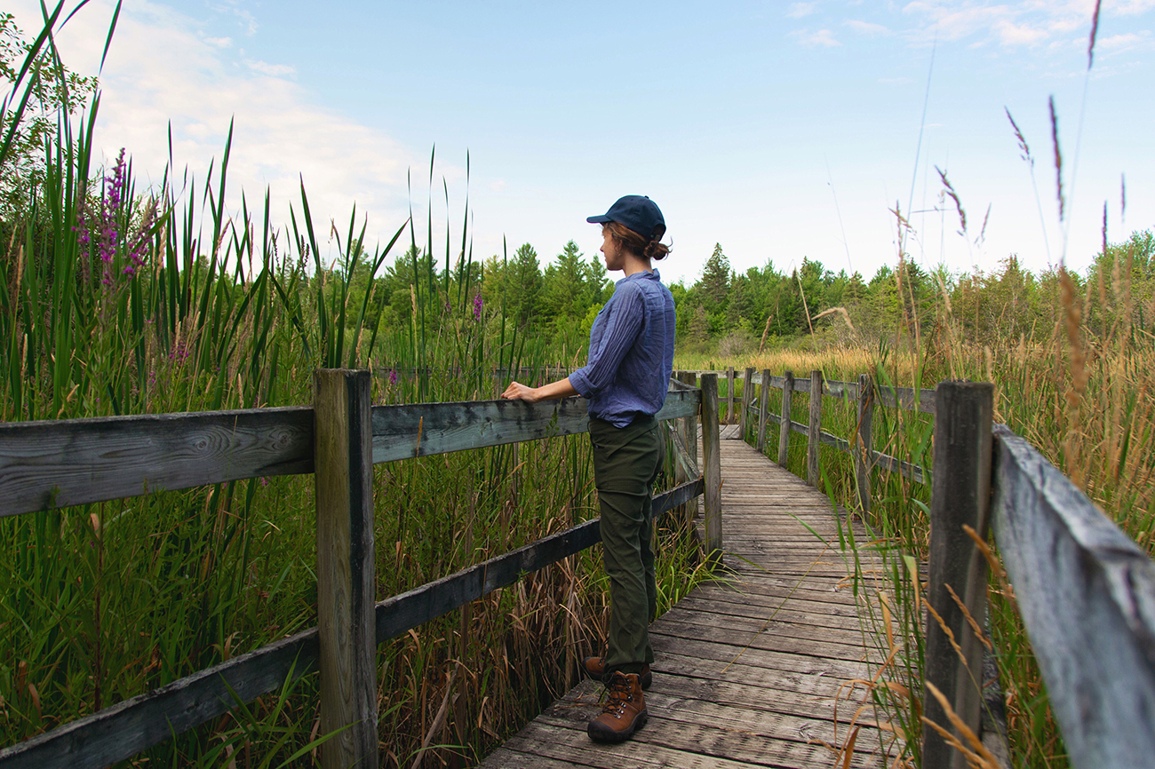 Woman stands on a boardwalk looking out over a marsh