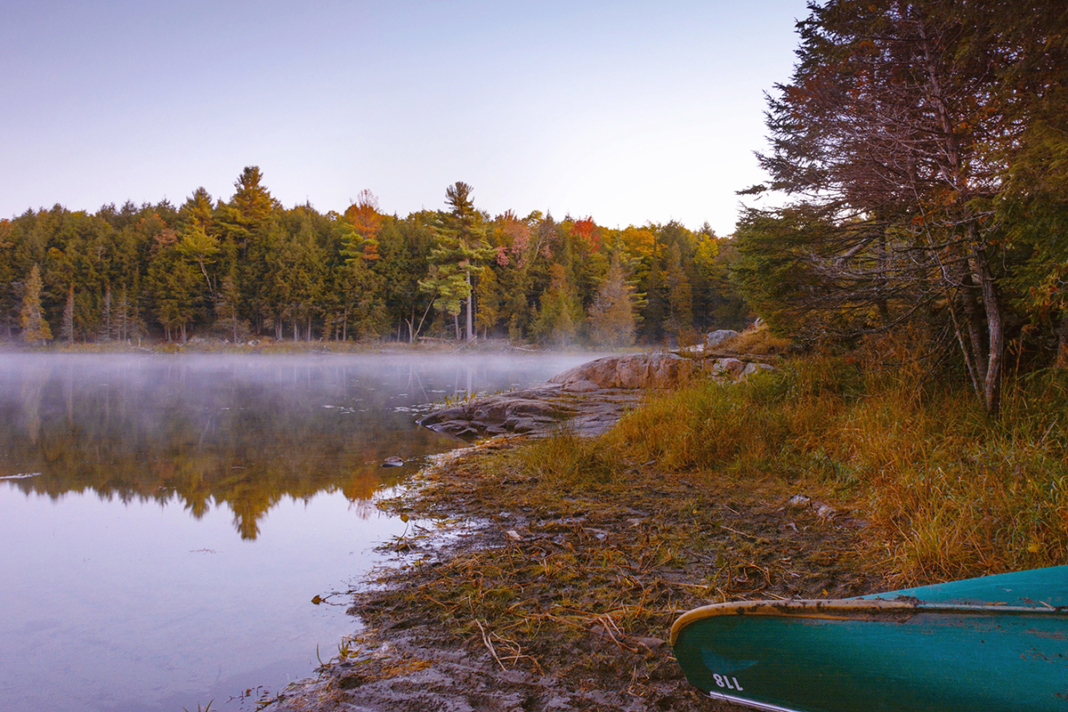 A canoe rest on the shoreline of a misty lake in Gatineau, Quebec