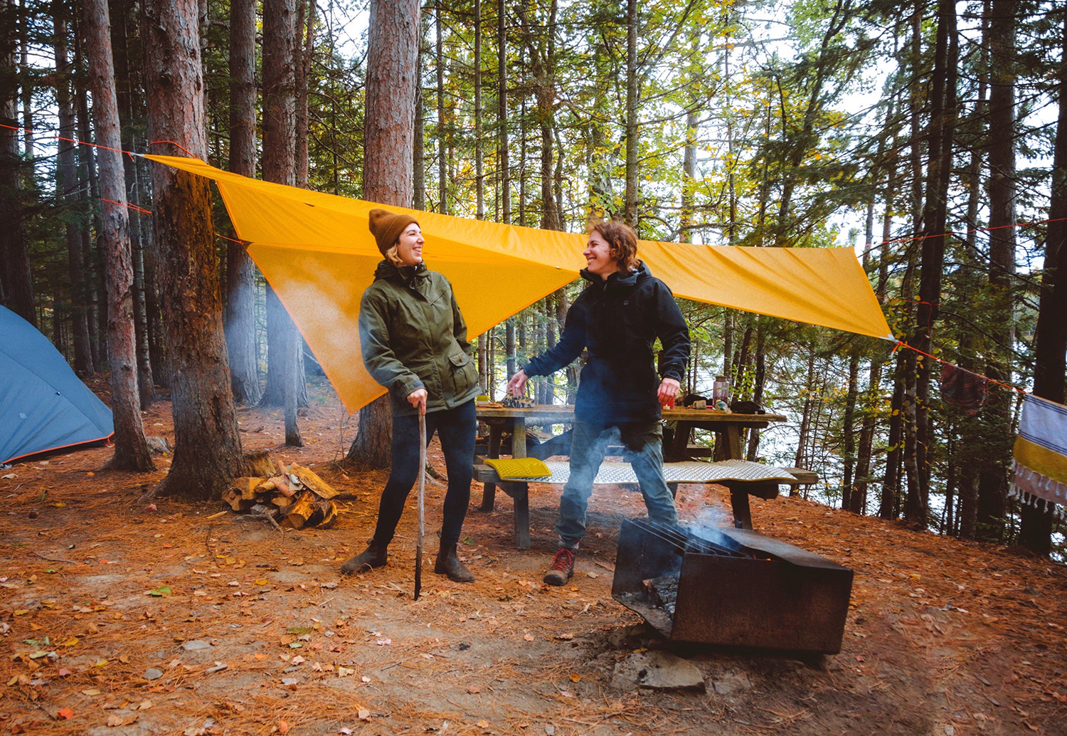 2 women are chatting and laughing at their campsite