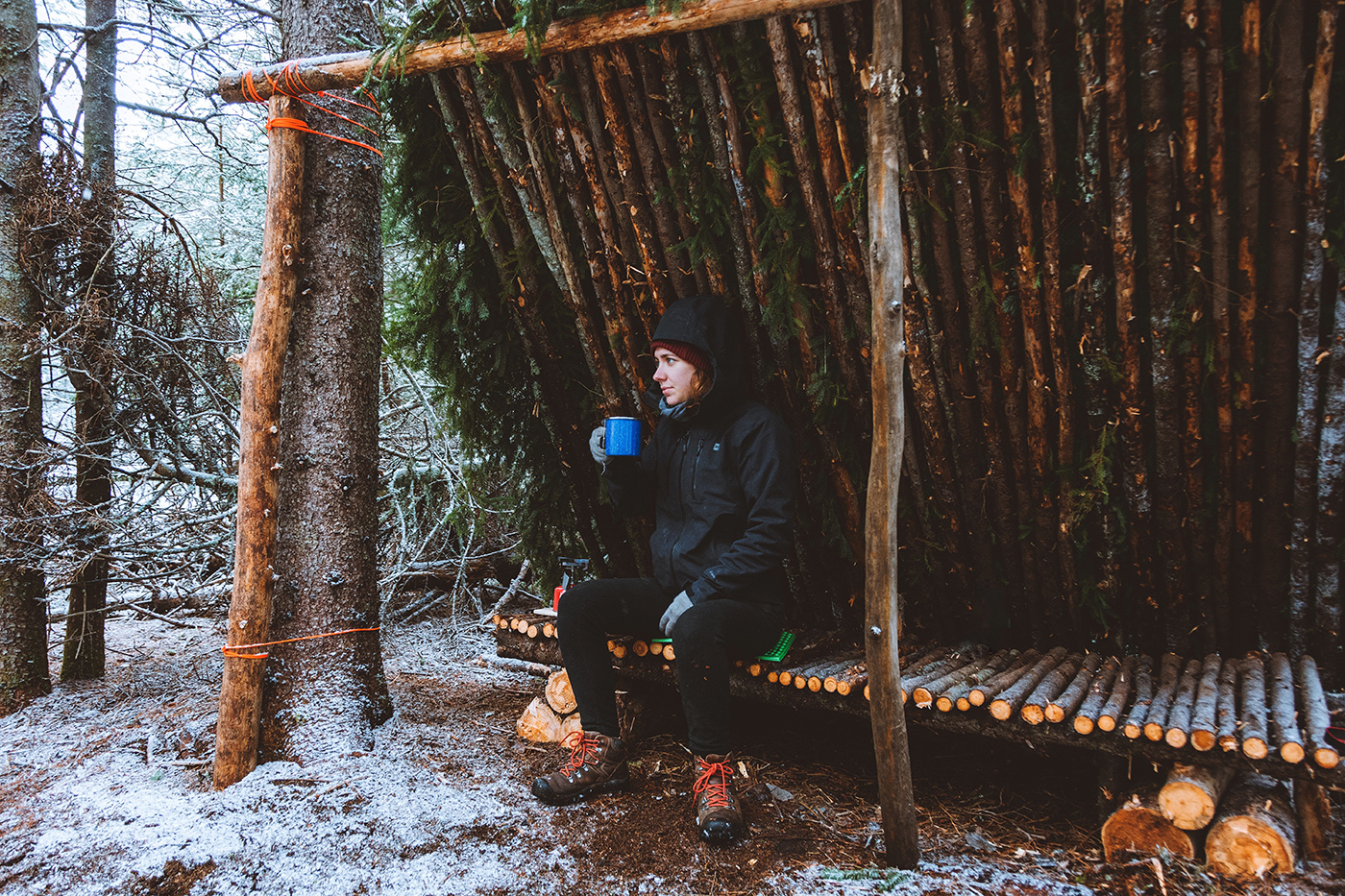 Woman sits in a lean to shelter made from logs and spruce boughs. She is drinking a cup of tea and there is snow on the ground.