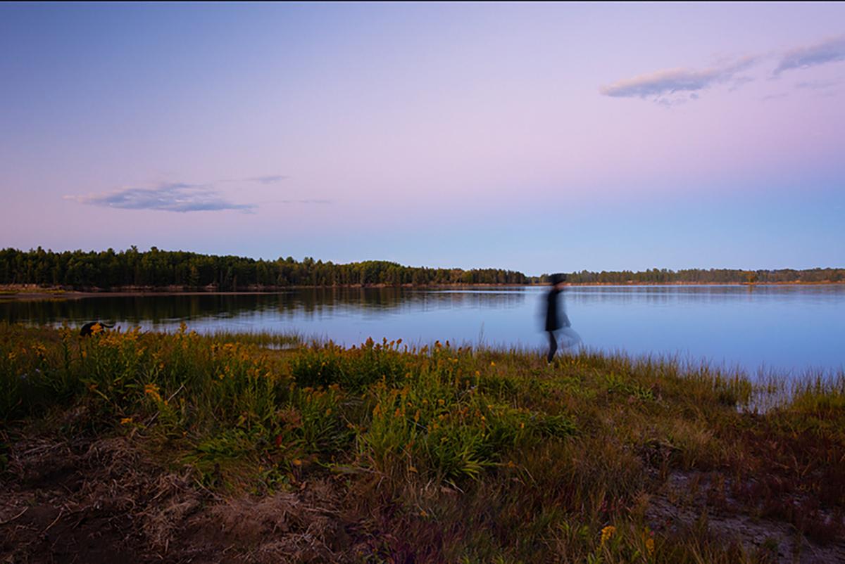 A woman walks along the Richibucto River in New Brunswick.