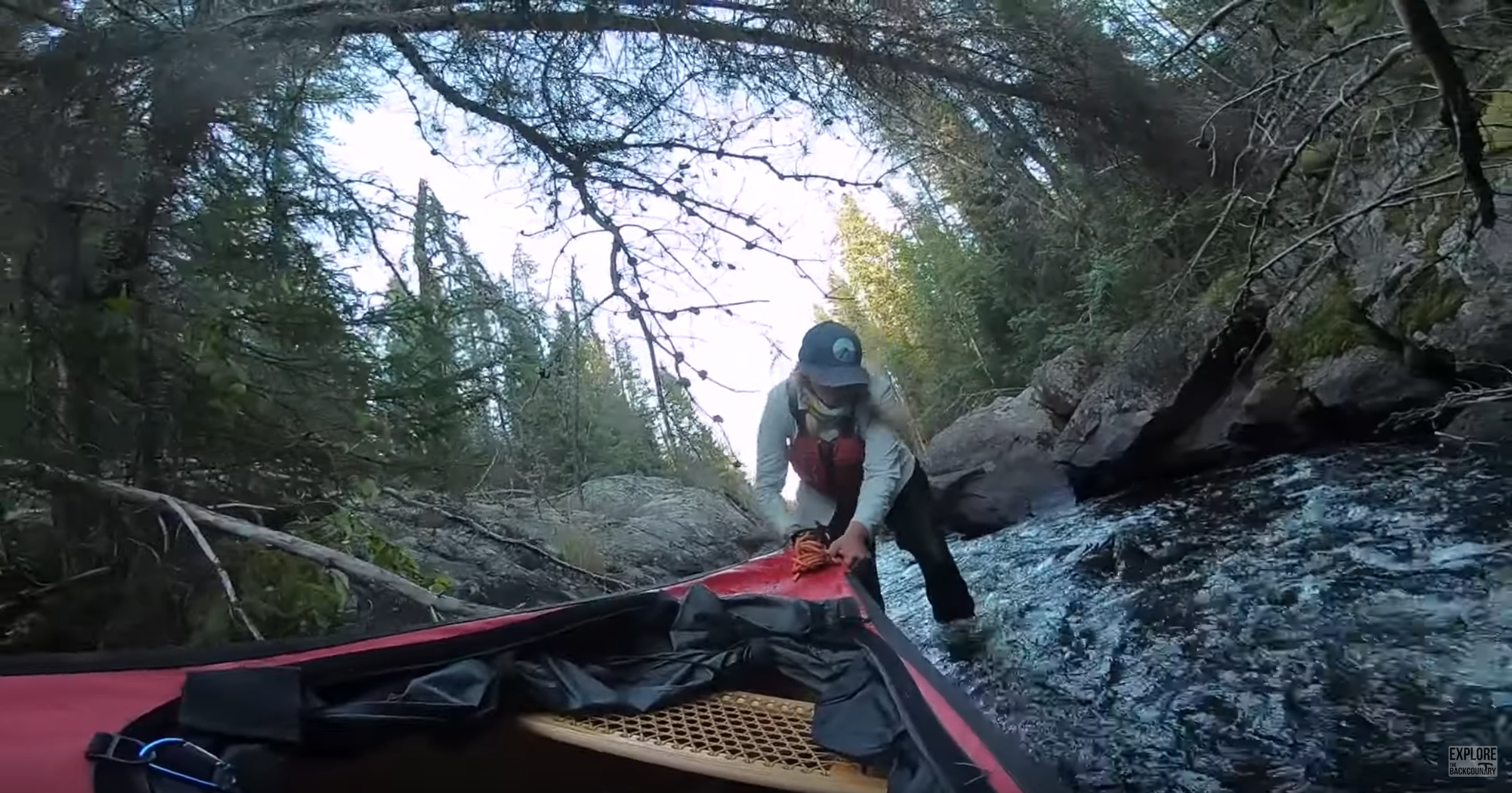 Leah pulls a canoe through a shallow river.  Screenshot from Explore the Backcountry by Brad and Wayne Jennings and Leah Schmidt.  Canadian outdoor adventure YouTubers