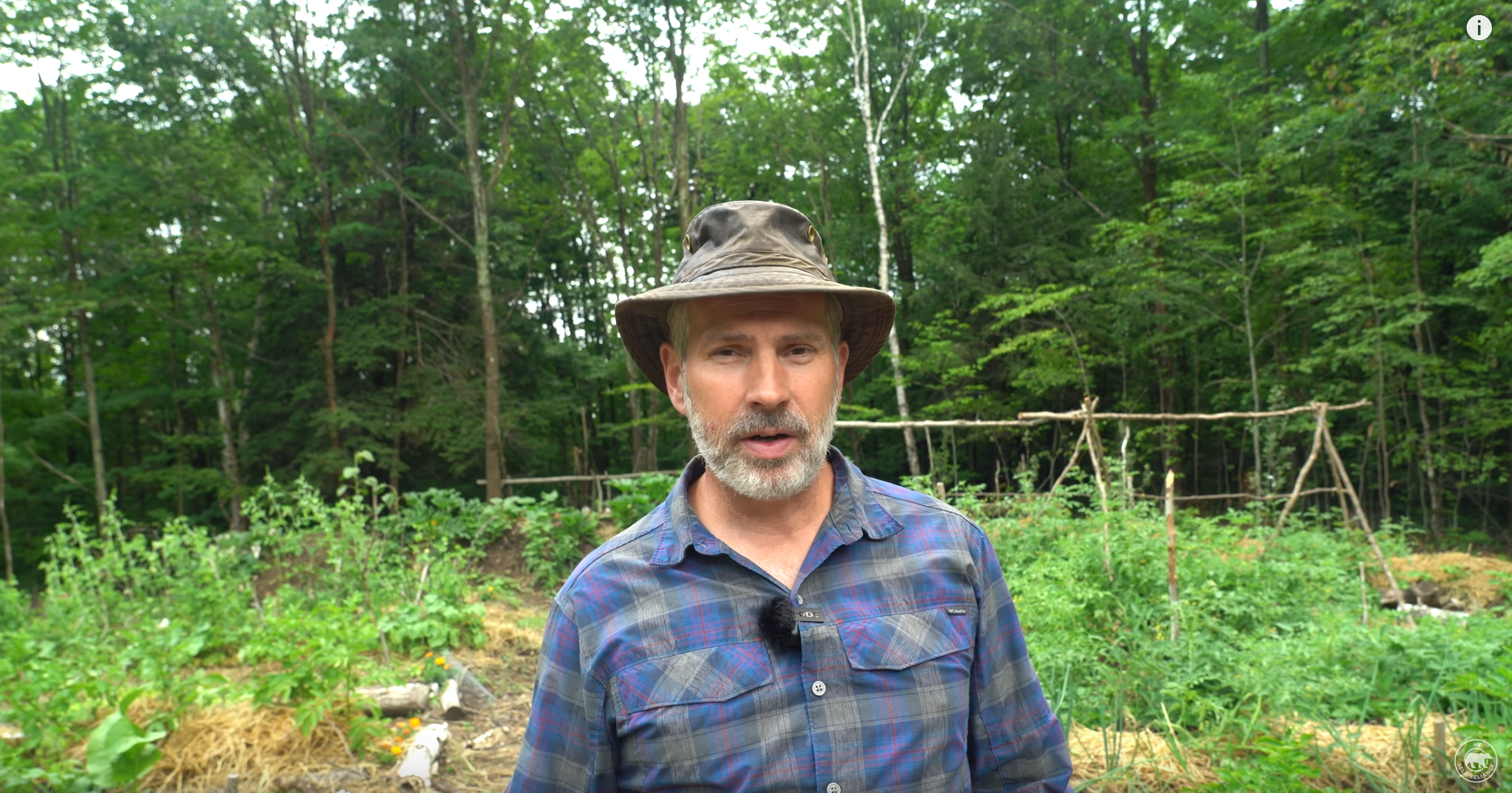 Shawn James stands in front of his forest garden.  Screenshot from My Self Reliance by Shawn James