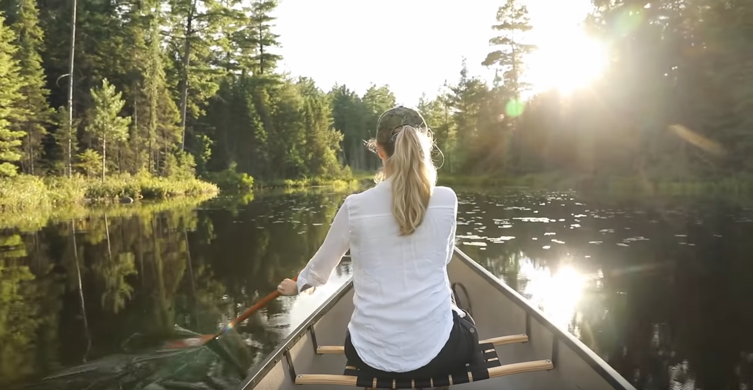 Caitlin paddles a canoe through a river at golden hour.  Screenshot from My Timber Life by Caitlin and Trustin Timber.